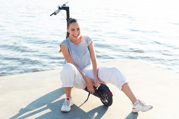 Belle femme souriante assise sur un scooter
