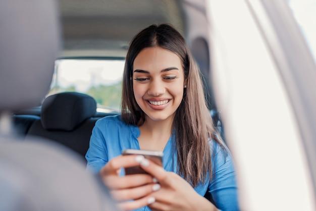 Belle femme souriante assise sur les sièges passager avant de la voiture.