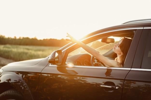 Belle femme souriante au volant de sa voiture le matin