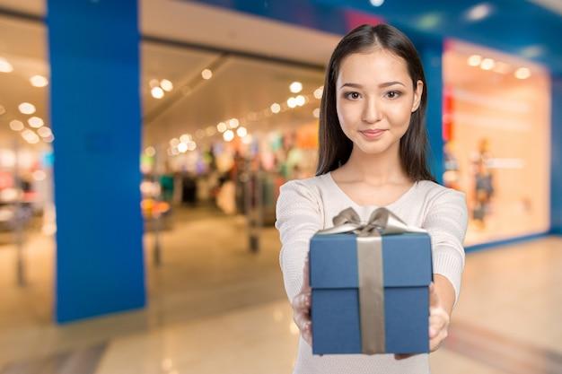 Belle femme souriante aux cheveux longs, tenant une boîte cadeau