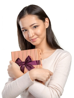 Belle femme souriante aux cheveux longs, tenant une boîte-cadeau