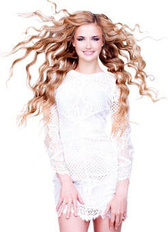 Belle femme souriante aux longs cheveux blonds bouclés. portrait complet du mannequin posant sur un mur blanc