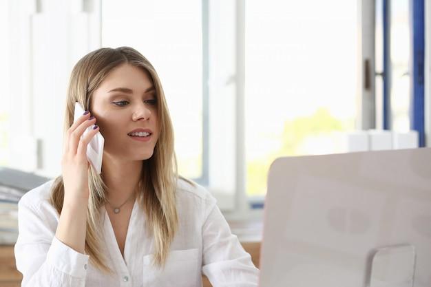 Belle femme souriante blonde parle téléphone portable en portrait de bureau.