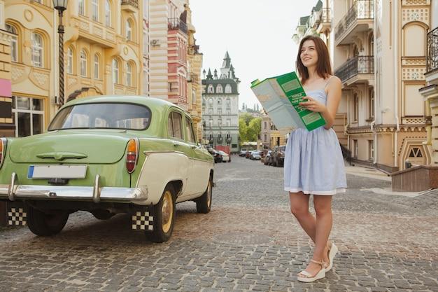 Belle femme souriante, cherche une place sur la carte, debout dans la rue