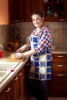 Belle femme souriante coupant du pain sur une planche à découper en bois