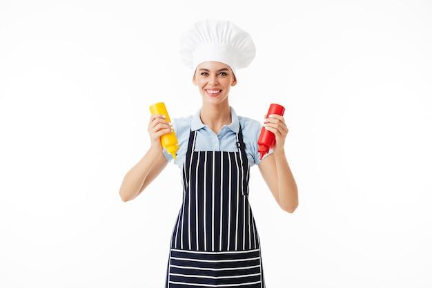 Belle femme souriante cuisinier en tablier rayé et chapeau blanc heureusement