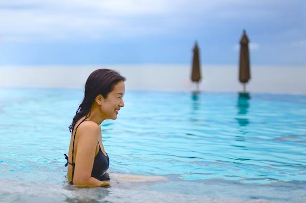 Belle femme souriante dans une piscine en vacances