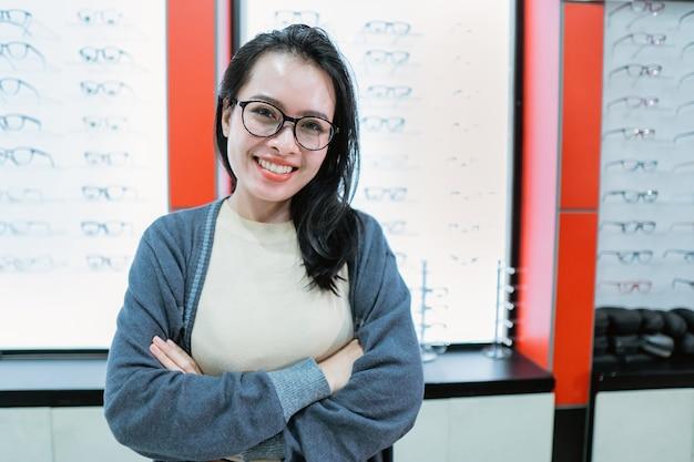 Une belle femme souriante est dans une clinique ophtalmologique avec un fond de fenêtre d'affichage de lunettes