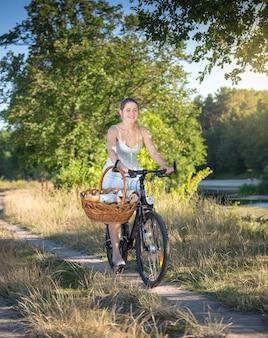 Belle femme souriante faisant du vélo au bord de la rivière à une journée ensoleillée