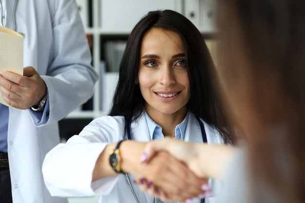 Belle femme souriante gp se serrant la main avec le visiteur