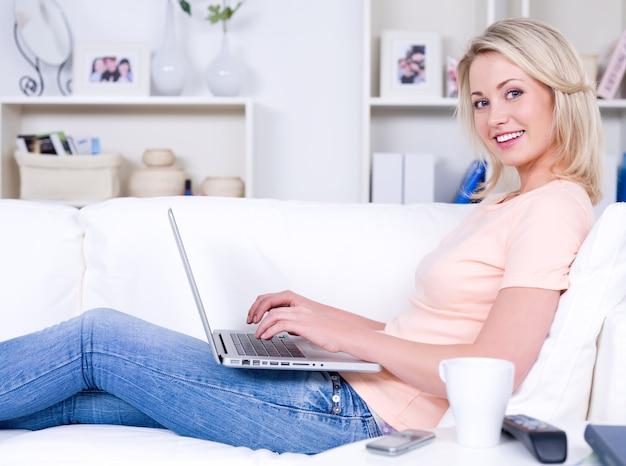 Belle femme souriante heureuse allongée sur le canapé avec ordinateur portable