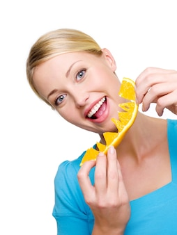 Belle femme souriante mange l'orange fraîche