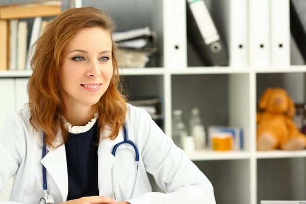 Belle femme souriante médecin debout dans le portrait de bureau