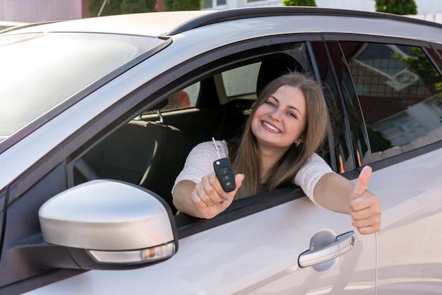 Belle femme souriante montrant la clé de la voiture à travers la fenêtre