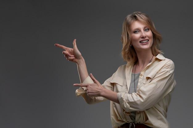 Belle femme souriante pointant des deux mains vers le fond sur son côté gauche sur un fond de studio gris.
