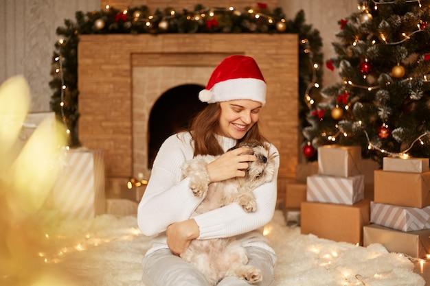 Belle femme souriante portant un pull blanc et un chapeau de père noël rouge jouant avec un chien pékinois dans un salon festif près de la cheminée et de l'arbre de noël, assise sur le sol sur un tapis moelleux.