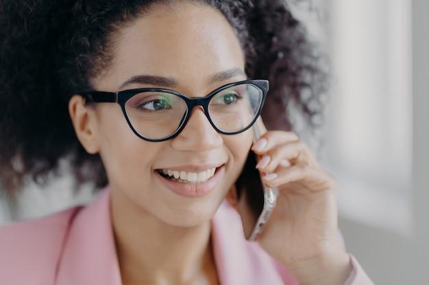 Belle femme souriante porte des lunettes optiques et détient un téléphone cellulaire moderne