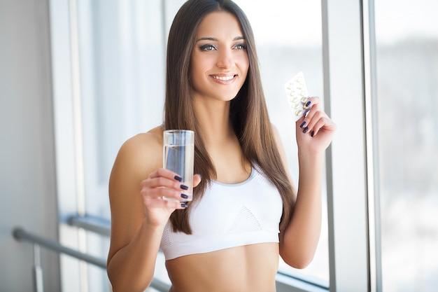 Belle Femme Souriante Prenant Des Comprimés De Vitamines Et Des Compléments Alimentaires Photo Premium