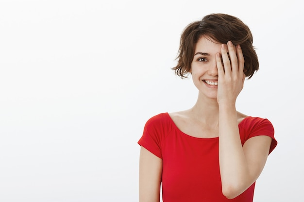 Belle femme souriante à la recherche de plaisir, couvrir la moitié du visage avec palm