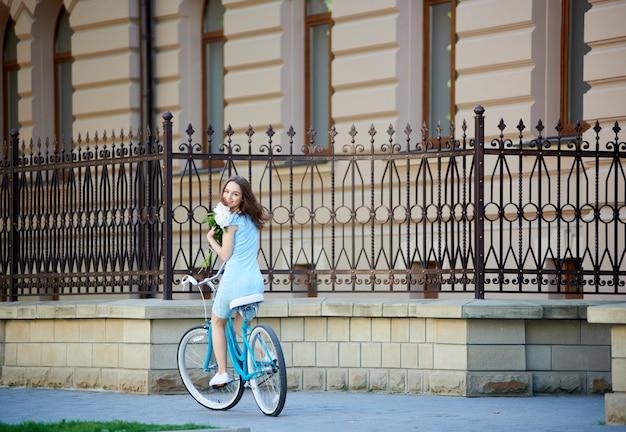 Belle femme souriante regardant en arrière tout en tenant des fleurs et en vélo bleu sur une jolie ville historique