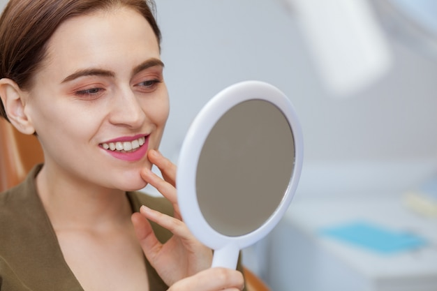 Belle femme souriante, regardant dans le miroir de la clinique dentaire