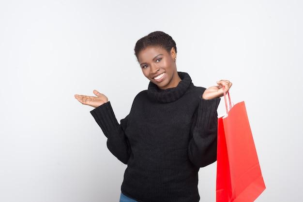 Belle femme souriante avec sac à provisions rouge