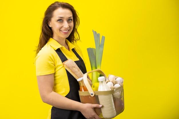 Belle femme souriante se tient à moitié avec boîte de légumes verts, lait, œufs, pain