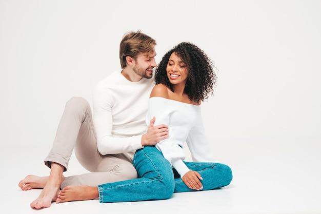 Belle femme souriante et son beau petit ami. joyeuse famille multiraciale joyeuse ayant des moments tendres sur gris