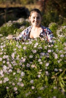 Belle femme souriante taille des fleurs au jardin avec des cisailles