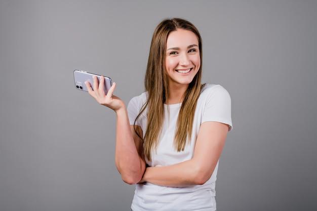 Belle femme souriante avec téléphone à la main isolé sur gris
