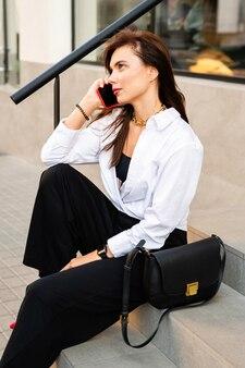 Belle femme souriante avec téléphone portable assis et parlant
