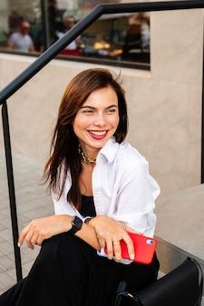 Belle femme souriante avec téléphone portable en riant. c'est une jeune femme d'affaires.