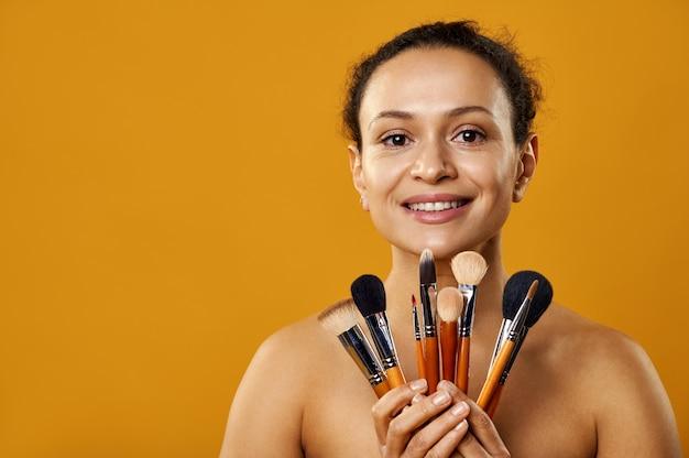 Une belle femme souriante et tenant des pinceaux de maquillage devant elle isolé sur fond jaune