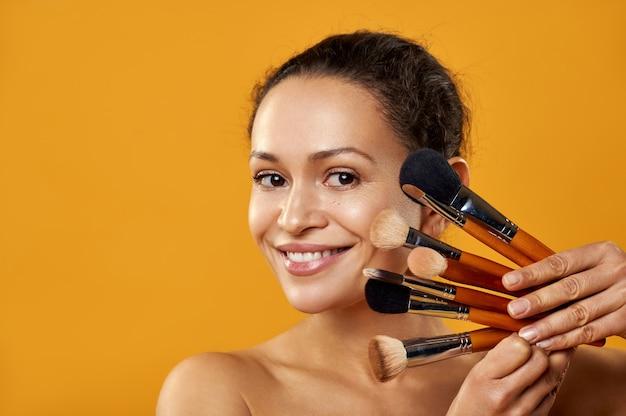La belle femme souriante et tenant des pinceaux de maquillage près du visage isolé sur fond jaune