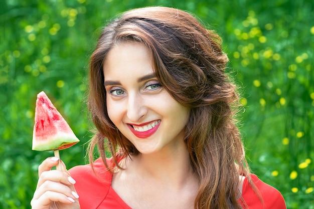 Belle femme souriante tient un morceau de pastèque sur fond d'herbe verte. concept de beauté d'été.