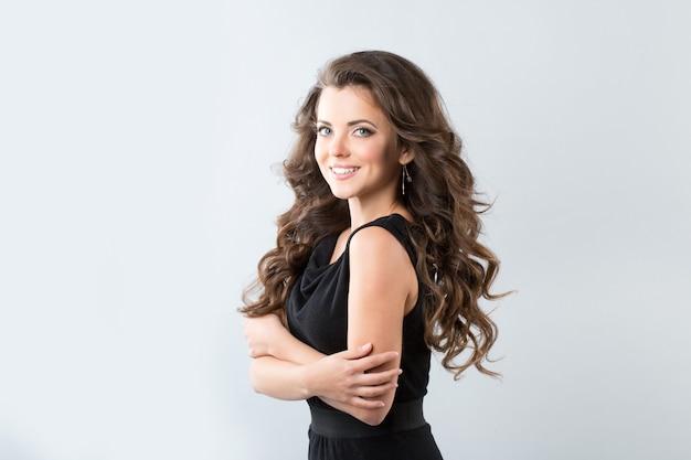 Belle femme souriante avec vent de cheveux longs.