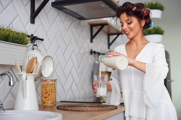 Belle femme souriante verse du lait frais d'une carafe dans un verre, dans l'élégante cuisine confortable du matin. concept d'alimentation et de régime alimentaire sain.
