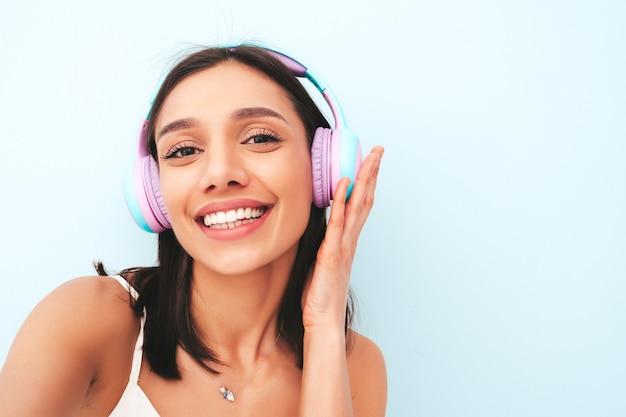 Belle femme souriante vêtue d'un pyjama blanc. modèle sans soucis écoutant de la musique dans des écouteurs sans fil