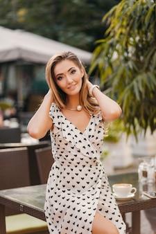 Belle femme souriante vêtue d'une robe imprimée blanche dans un style romantique posant dans un café de rue par une journée ensoleillée