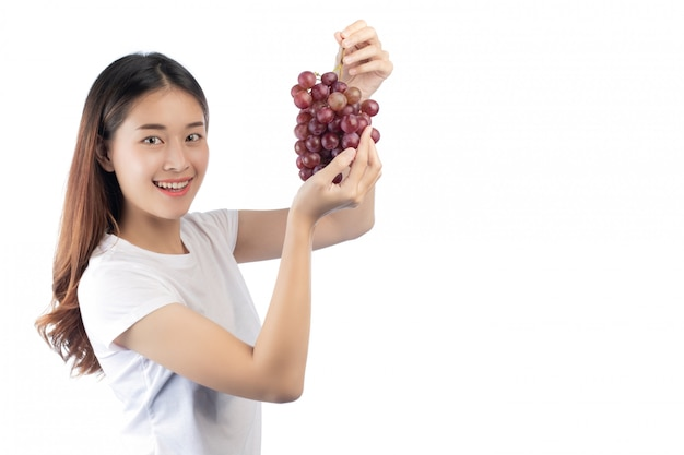 Belle femme avec un sourire heureux, tenant un raisin de la main, isolé sur fond blanc.