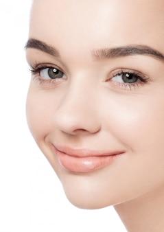 Belle femme avec un sourire mignon maquillage naturel spa soins de la peau portrait sur fond blanc