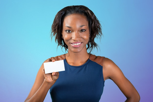 Une belle femme avec un sourire parfait détient une carte de visite