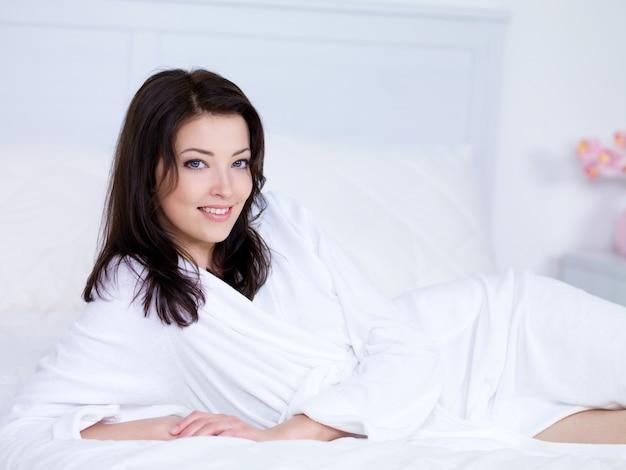 Belle femme avec sourire relaxant sur un lit à la maison