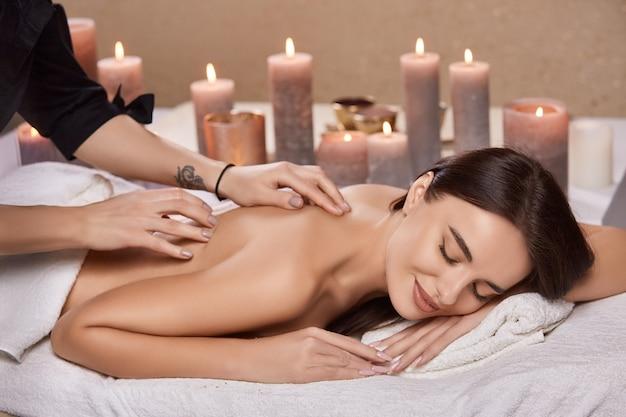 Belle femme avec le sourire sur le visage relaxant et ayant un massage dans un salon de beauté