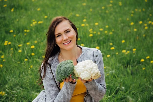 Belle femme sourit et tient le brocoli et le chou-fleur dans ses mains