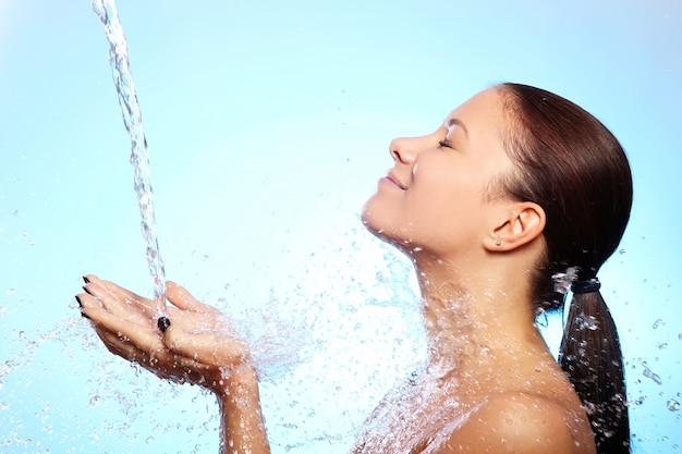 Belle femme sous les éclaboussures d'eau