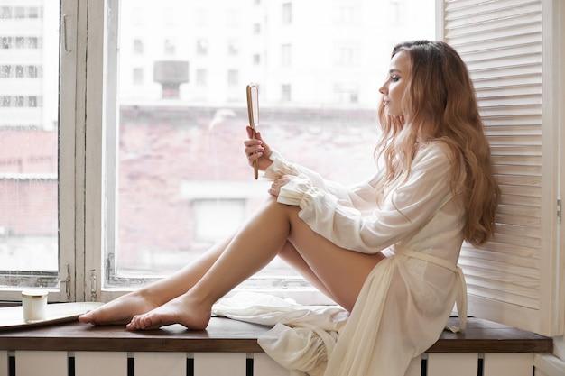 Belle femme en sous-vêtements blancs et déshabillé à la maison dans la salle de bain. une femme amoureuse se repose