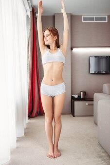 Belle femme en sous-vêtements, faire des exercices du matin dans la chambre. fille se réveiller