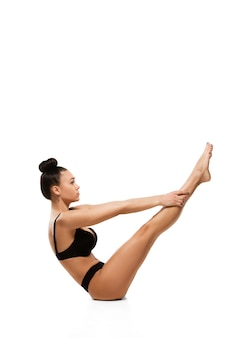Belle femme en sous-vêtements isolé sur mur blanc. beauté, cosmétiques, spa, épilation, traitement et concept de remise en forme. corps en forme et sportif, sensuel avec une peau soignée, faisant des exercices.