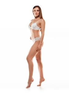 Belle femme en sous-vêtements isolé sur mur blanc